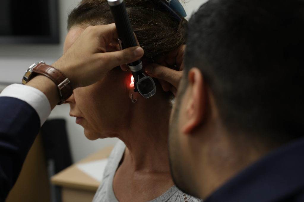 The hearing specialist inspecting an ear.